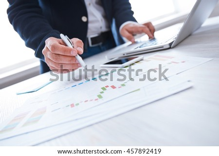 Young businessman working  in the office. Notebook and smartphone on wood table, papers, documents, statistics