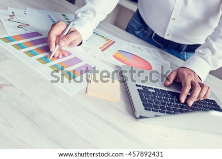 Young businessman working  in the office. Notebook on wood table, papers, documents, statistics