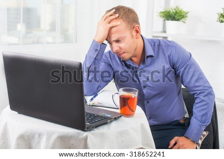 Young businessman working in the office, very concerned, solves the problem, and leaned his head on his hand. - stock photo