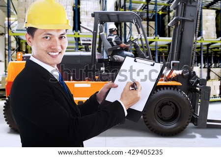Young businessman working in the warehouse while holding a clipboard with a forklift on the background - stock photo