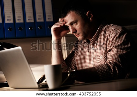 Young businessman working late on laptop at night in dark office - stock photo