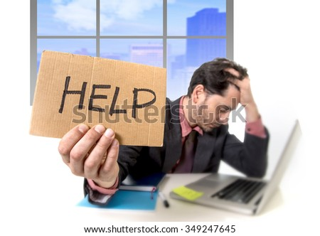 young businessman working on computer laptop asking for help holding cardboard sign looking desperate and depressed in stress overwhelmed and overwork at business district office - stock photo