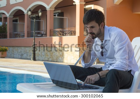 Young businessman working on his laptop by the pool while in sunbed - stock photo