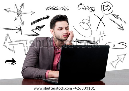 Young businessman working on his laptop  keeping hand on chin and thinking how to solve a problem with symbols on his back - stock photo