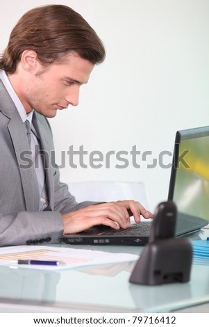 Young businessman working on laptop - stock photo
