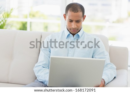 Young businessman working on laptop on the couch in the office