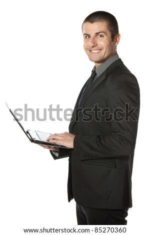 Young businessman working on laptop over white background - stock photo