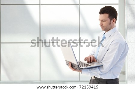 Young businessman working on laptop, standing in office lobby.? - stock photo