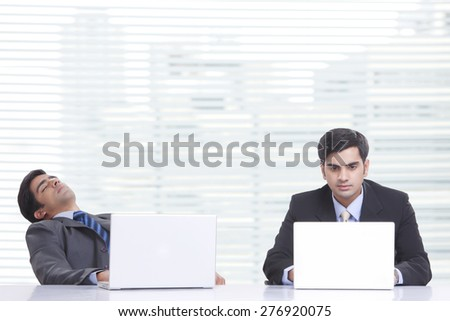 Young businessman working on laptop while colleague sleeping at desk in office - stock photo