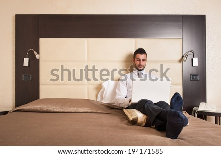 Young businessman working with computer sit on bed in hotel room.