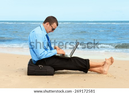 young businessman working with laptop on the beach  - stock photo