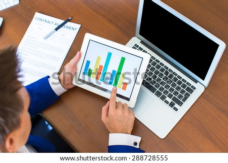 Young businessman working with modern devices, digital tablet computer and cellphone - stock photo