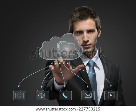 Young businessman working with virtual technology touching the arrow on the chart - stock photo