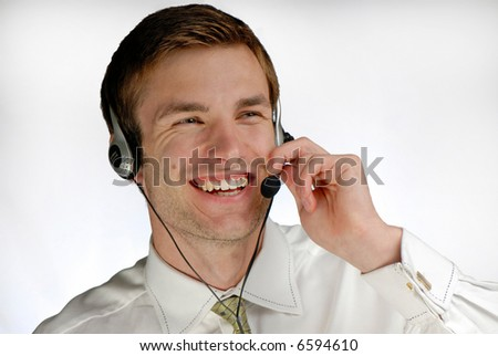 young  businessman works in headphones with  microphone on white background