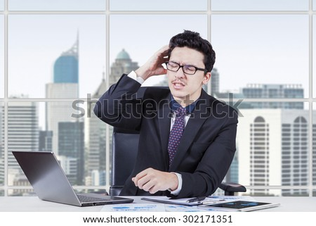 Young businessman worrying his job while scratching his head in the office - stock photo