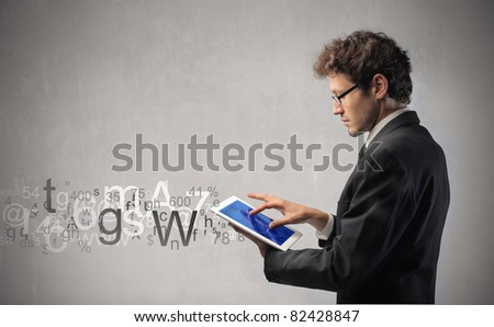 Young businessman writing on a tablet - stock photo