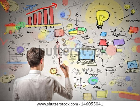 young businessman writing on the wall - stock photo