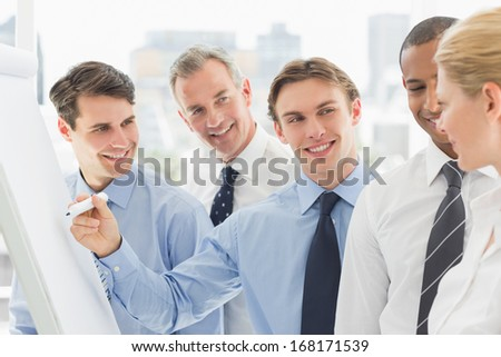 Young businessman writing on whiteboard with colleagues in the office - stock photo