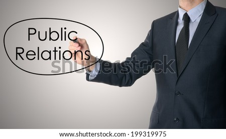 Young businessman writing Public Relations on grey background