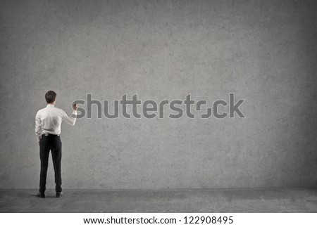 Young businessman writing something on a large empty wall - stock photo