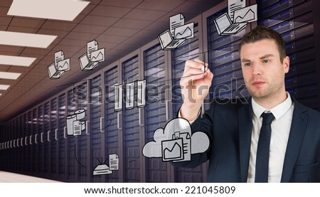 Young businessman writing with marker against digitally generated server room with towers - stock photo