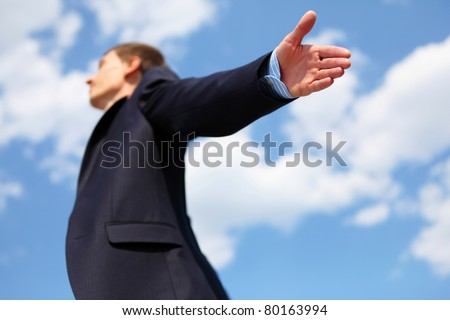 young businessmanin a blue suit embracing air against blue sky - stock photo