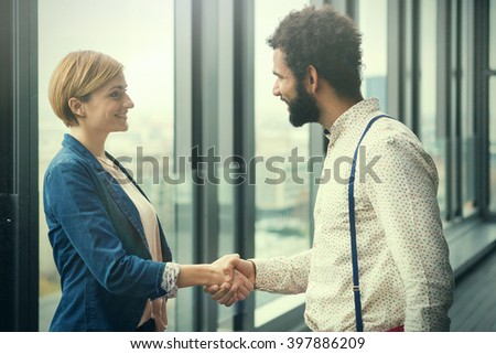 Young businessmen and business woman shaking hands in modern office hall. Post processed with cyan vintage film filter. - stock photo