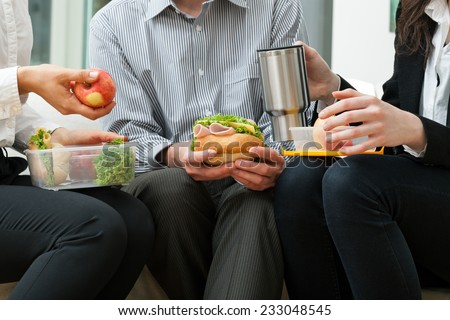 Young businessmen eating homemade lunch during break - stock photo