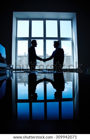 Young businessmen greeting one another by handshake - stock photo