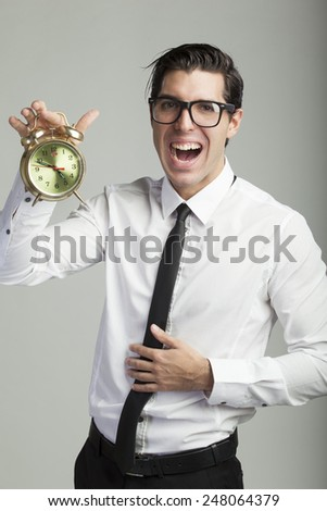 young businessmen on grey background holding alarm clock stressed out by deadline - stock photo