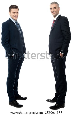 Young businessmen posing with hands in pockets - stock photo