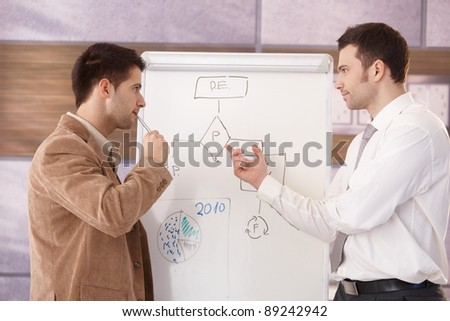 Young businessmen presenting together over whiteboard.? - stock photo