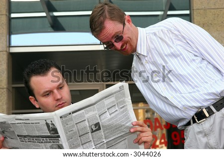 Young businessmen reading newspapers - stock photo