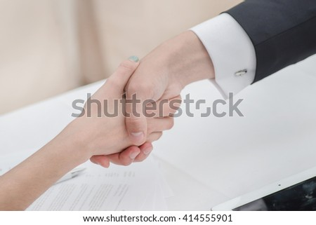 Young businessmen shaking hands with each other in the business center. Successful businessmen on a corporate meeting. Female hand shakes man's hand close-up view - stock photo