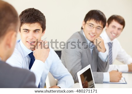 Young businessmen sitting at seminar