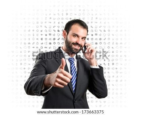 Young businessmen talking to mobile over grey background.  - stock photo