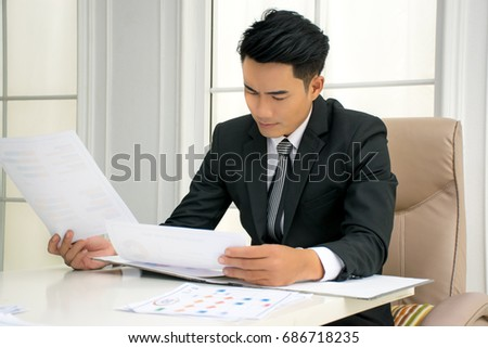 Young businessmen who is wearing black jacket is reading and checking the information on the documents at the office