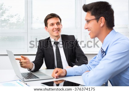 Young businessmen working in office with laptop. - stock photo