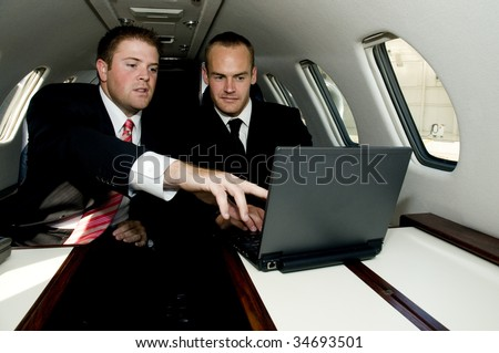 Young businessmen working on a laptop in a corporate jet. - stock photo