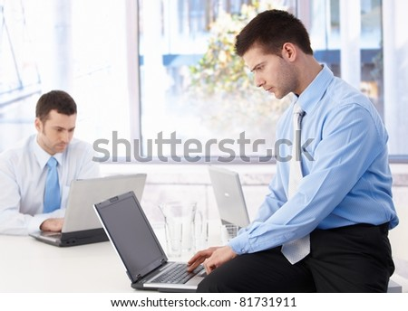 Young businessmen working on laptop in bright office.? - stock photo