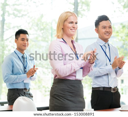 Young businesspeople applauding at the conference on the foreground  - stock photo