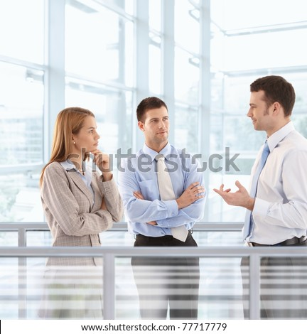 Young businesspeople chatting in modern office lobby.? - stock photo