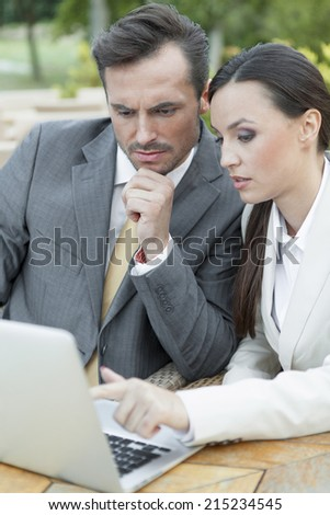 Young businesspeople discussing over laptop outdoors - stock photo