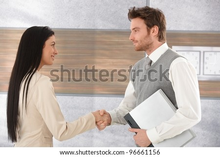Young businesspeople greeting each other by shaking hands, smiling.? - stock photo