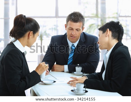 Young businesspeople having a business meeting at coffee table in office lobby.