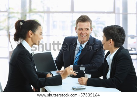 Young businesspeople having a business meeting at coffee table in office lobby, using laptop computer. Copyspace on blank screen. - stock photo