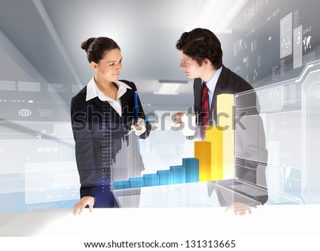 young businesspeople looking at graph of high-tech image - stock photo