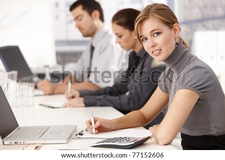 Young businesspeople sitting at meeting table in office, having business training, writing notes.? - stock photo