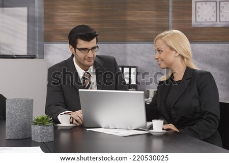Young businesspeople sitting at table in meetingroom, working with laptop computer, drinking coffee. - stock photo
