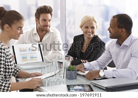 Young businesspeople sitting in meetingroom, having meeting, chatting in good mood. - stock photo